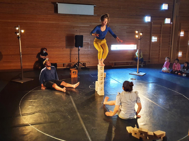 Tre personer i en opptegnet sirkel på gulvet, den ene kvinnen balanserer på en stabel med klosser