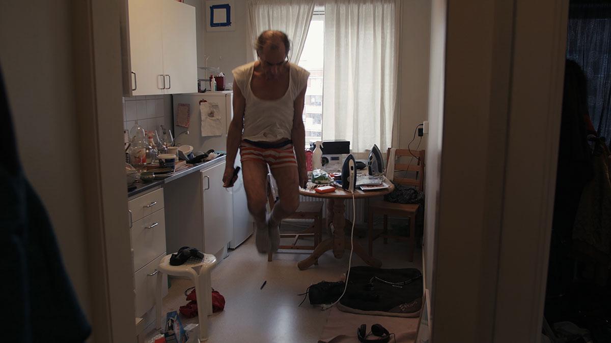 """Stillbilde fra filmen """"Røverdatter"""". Faren til regissør Sofia Haugan hopper inne på et kjøkken."""