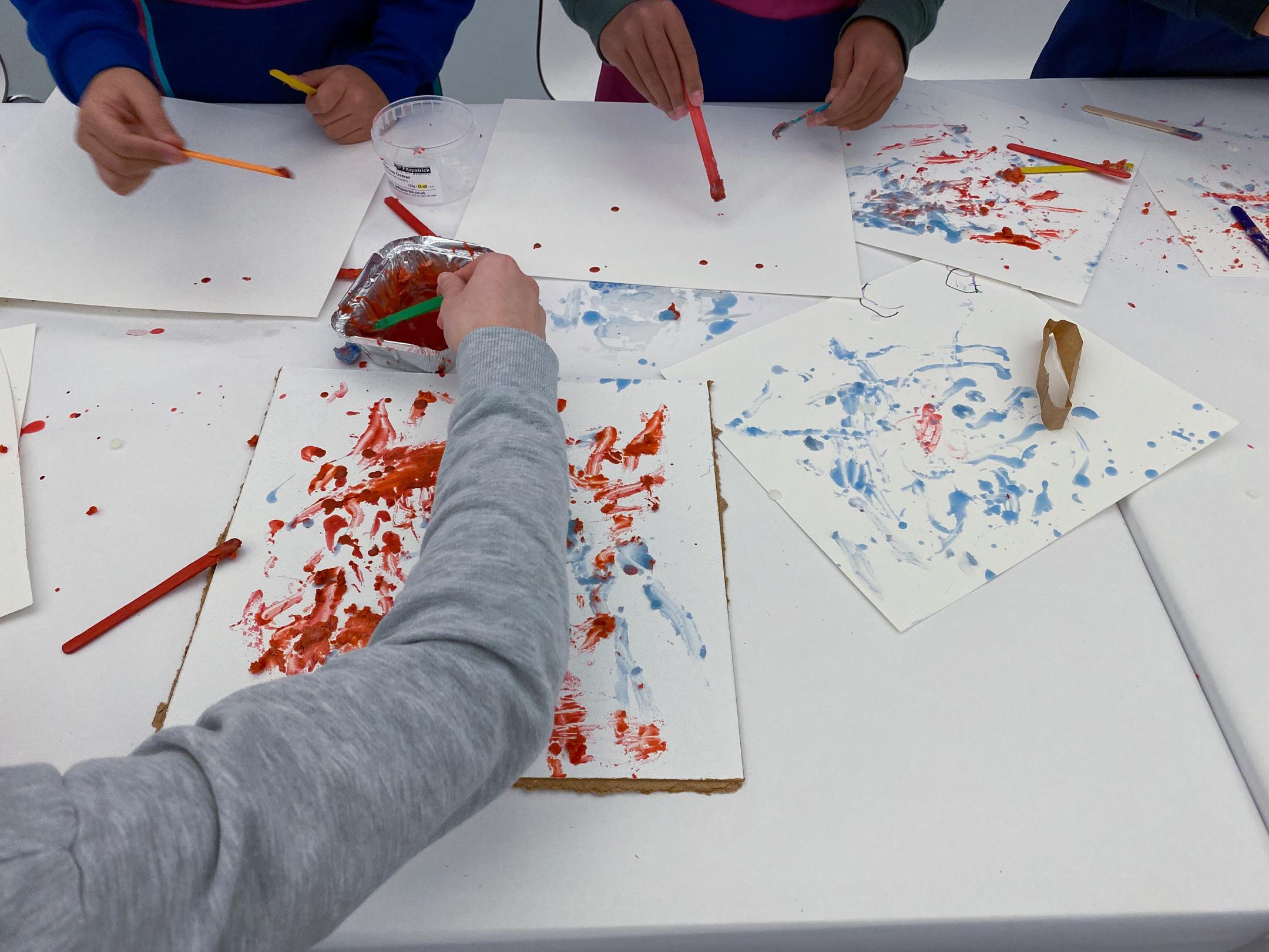 En hånd maler med rødt og blått på papirer som ligger strødd utover et bord